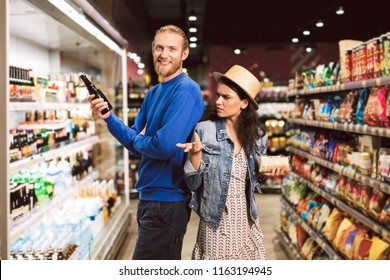 Young smiling guy happily looking in camera holding beer in hand while girl thoughtfully looking at him in modern supermarket