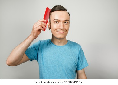 Young smiling guy holds a comb and combs his hair, isolated on a white background.