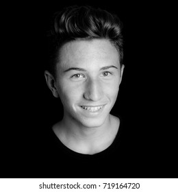 young smiling guy portrait on black background - black and white photo