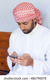 Young smiling handsome arabic man in traditional clothes uses smartphone