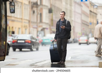 Young smiling handsome man in 20s with luggage bag standing on rainy city street with busy traffic transport using smartphone, waiting for public bus, traveling, wearing casual style clothes