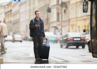 Young smiling handsome man in 20s with luggage bag standing on rainy city street with busy traffic transport using smartphone, standing on bus stop, travelling, wearing casual style clothes