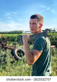 Young smiling handsome man in green clothes with wrench. Outdoor in country side.