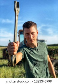 Young smiling handsome worker in green clothes hold wrench. Outdoor in country side, on tractor background.