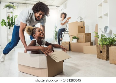 Young Smiling Happy African-american Family Unpacking During Move. New Home. Little preschooler daughter sitting in cardboard box, father rolling her. Smiling mother looking them.