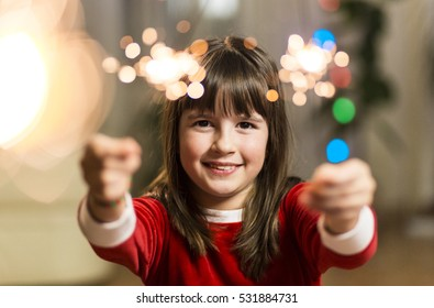 Young smiling happy girl having fun with sparkler before coloured lights background