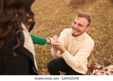 Young smiling happy man kneeling proposing to young woman, 20-29 years old, alone on mountain field. Autumn.