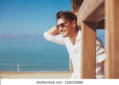 Young smiling happy man on beach vacation. With sunglasses, overlooking the blue sea. Relaxed on a wooden frame. Intense daylight.