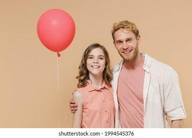 Young smiling happy parent man with child teen girl wear casual clothes Daddy kid daughter celebrate birthday party and hold red air inflated helium balloon look camera isolated on beige background.