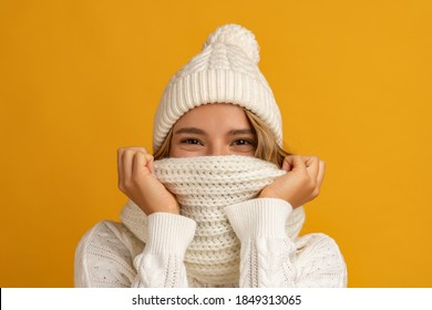 young smiling happy pretty blond woman wearing white knitted sweater, scarf and hat, warm winter cold season fashion accessories trend, posing on yellow studio background isolated - Shutterstock ID 1849313065