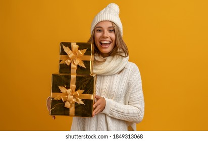 young smiling happy pretty woman holding golden present boxes celebrating new year, christmas gifts, wearing white knitted sweater, scarf and hat, winter fashion trend, posing on yellow background