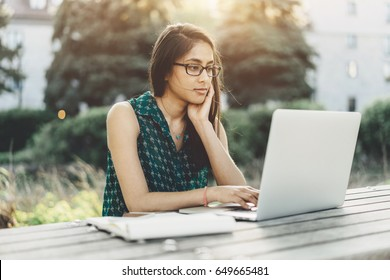 Young smiling hipster girl using laptop for work while sitting at outdoor cafe, Female student studying at park and using modern laptop at sunny day
