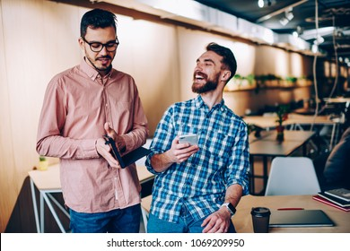 Young smiling hipster guy laughing at funny story telling by colleague on break in office, emotional cheerful man joking on friend networking on smartphone getting his funny pictures of email