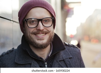 Young smiling hipster with moustache, beard and glasses