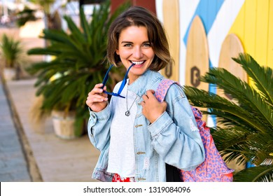 Young smiling hipster woman posing outdoor near palm trees beach cafe, wearing denim jacket and bright backpack, spring summer travel mood.