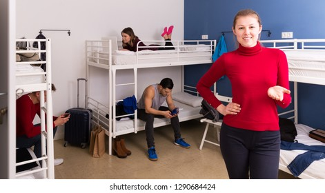 Young smiling hostess of hostel showing guests common bedroom