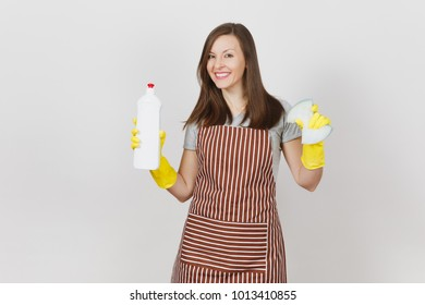 Young smiling housewife in yellow gloves, striped apron isolated on white background. Attractive woman holding bottle with cleaner liquid for washing and cleaning sponge. Copy space for advertisement
