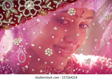 Young smiling Indian Bride looking through traditional veil shy muslim beautiful