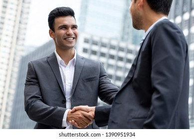 Young smiling Indian businessman making handshake with partner in the city for greeting, dealing, merger and acquisition concepts