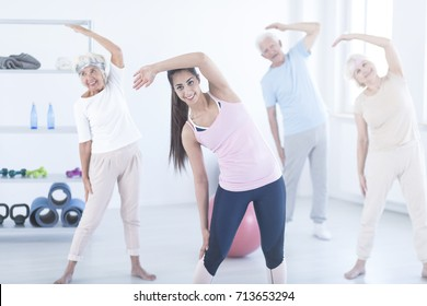 Young smiling instructor showing stretch exercise to elderly people at fitness studio