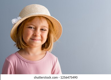 Young smiling kid girl in straw hat and pink t-shirt bust front portrait against plain grey wall with copy space