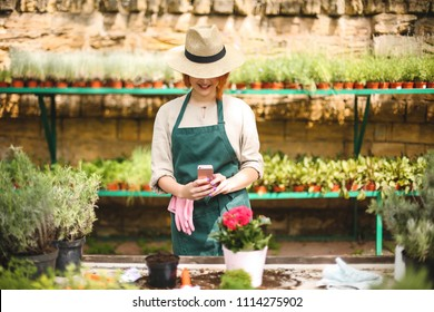 Young smiling lady in apron and hat standing and taking photos of flower in pot on her cellphone while working in greenhouse