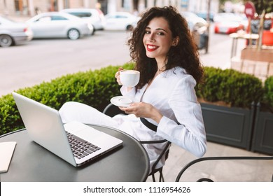 Young smiling lady with dark curly hair in white costume sitting at the table with laptop and cup of coffee in hands while joyfully looking in camera in cafe on street
