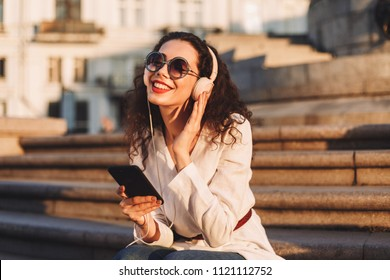 Young smiling lady with dark curly hair in sunglasses and white jacket sitting on stairs with cellphone in hand and dreamily listening music in headphones on street