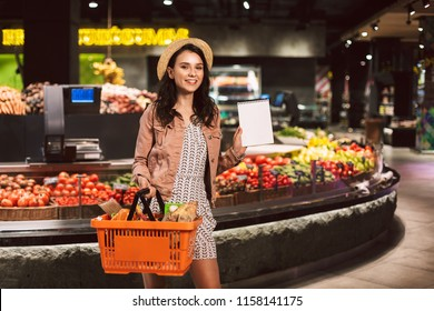Young smiling lady in hat holding basket full of products happily looking in camera showing shopping list in modern supermarket