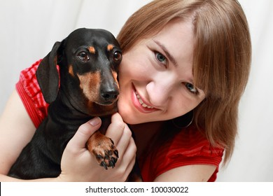 Young smiling lady hugging her Dachshund dog