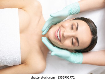 Young smiling lady looking delighted while lying with her eyes closed and hands in rubber gloves touching her cheeks