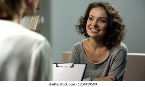 Young smiling lady at rehab therapy session, help from psychologist, improvement