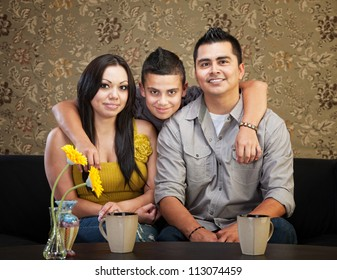 Young smiling Latino family sitting indoors together