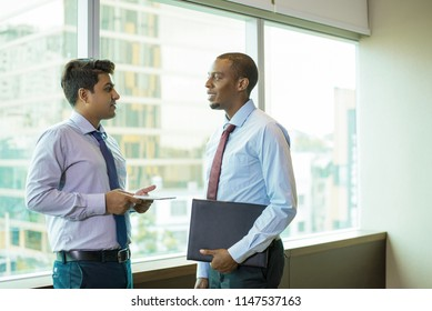 Young smiling lawyer consulting his client in office hallway. Cheerful young entrepreneurs discussing current problems and plans. Busines meeting concept