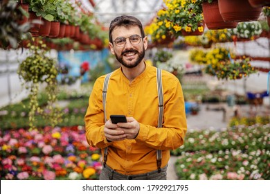 Young smiling male entrepreneur standing at hothouse and taking orders online. Hothouse interior.