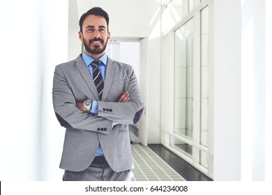 Young smiling male intelligent professor dressed in suit is posing for camera,while is standing in university hallway. Happy businessman is resting after successful signing a contract with new partner