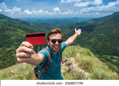 Young smiling male showing empty credit card. He is standing on top of mountain and showing the outdoor beauty. Concept of easy travelling