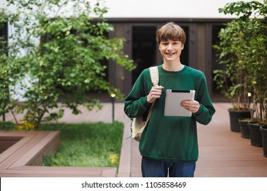Young smiling man with backpack standing and happily looking in camera with tablet in hand in courtyard of university
