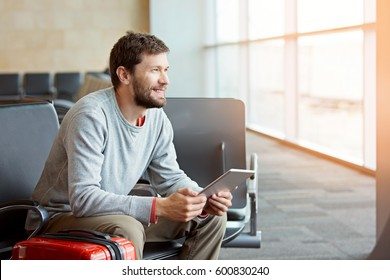 young smiling man with beard holding tablet in hands working in airport while waiting for plane departure, sun flare from the window