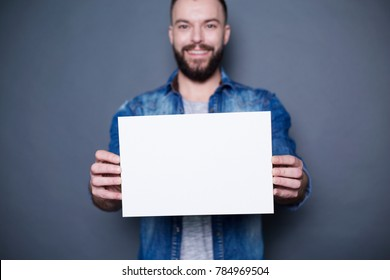 Young smiling man in a denim shirt shows a white sheet of paper in the camera on a gray background. Area for advertising.