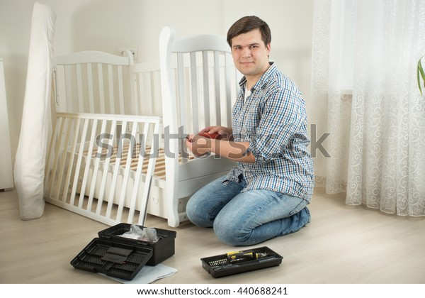Young smiling man disassembling furniture in nursery