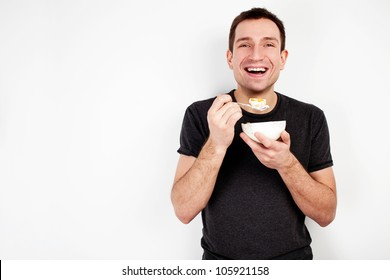Young smiling man eating cereal on diet isolated on white background