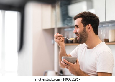 Young smiling man eating cereal on diet isolated on white background.