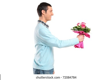 Young smiling man giving flowers isolated against white background