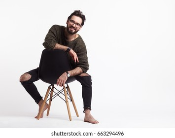 Young smiling man in glasses and casual clothing sitting on chair and looking at camera on white.