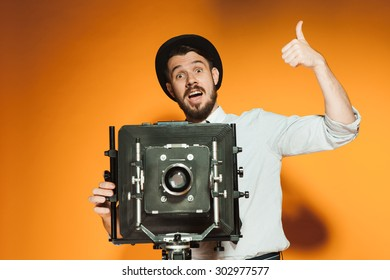Young smiling man in hat as photographer with retro camera on an orange background