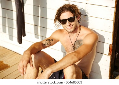 Young smiling young man in hat and sunglasses sitting at the surf shack