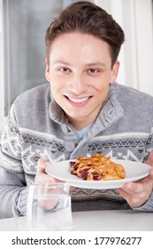 young smiling man holding dessert on the plate