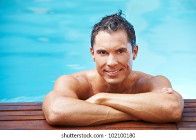 Young smiling man leaning at edge of swimming pool