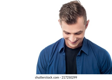 Young smiling man looking down isolated on white